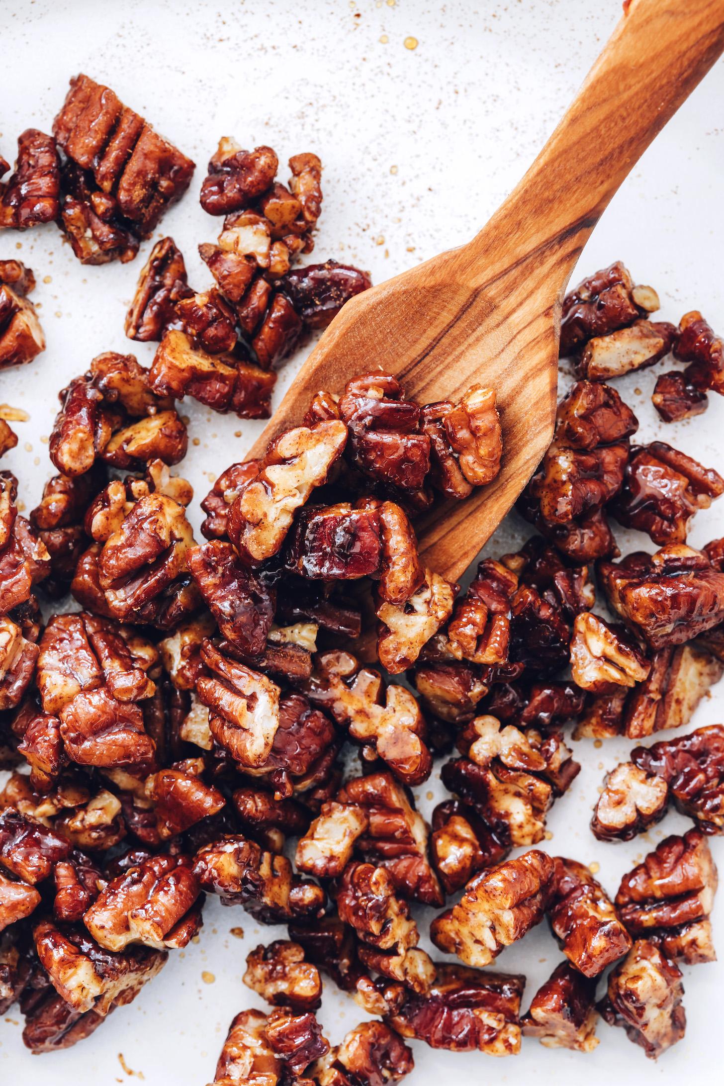 Cuillère en bois tenant des noix de pécan confites