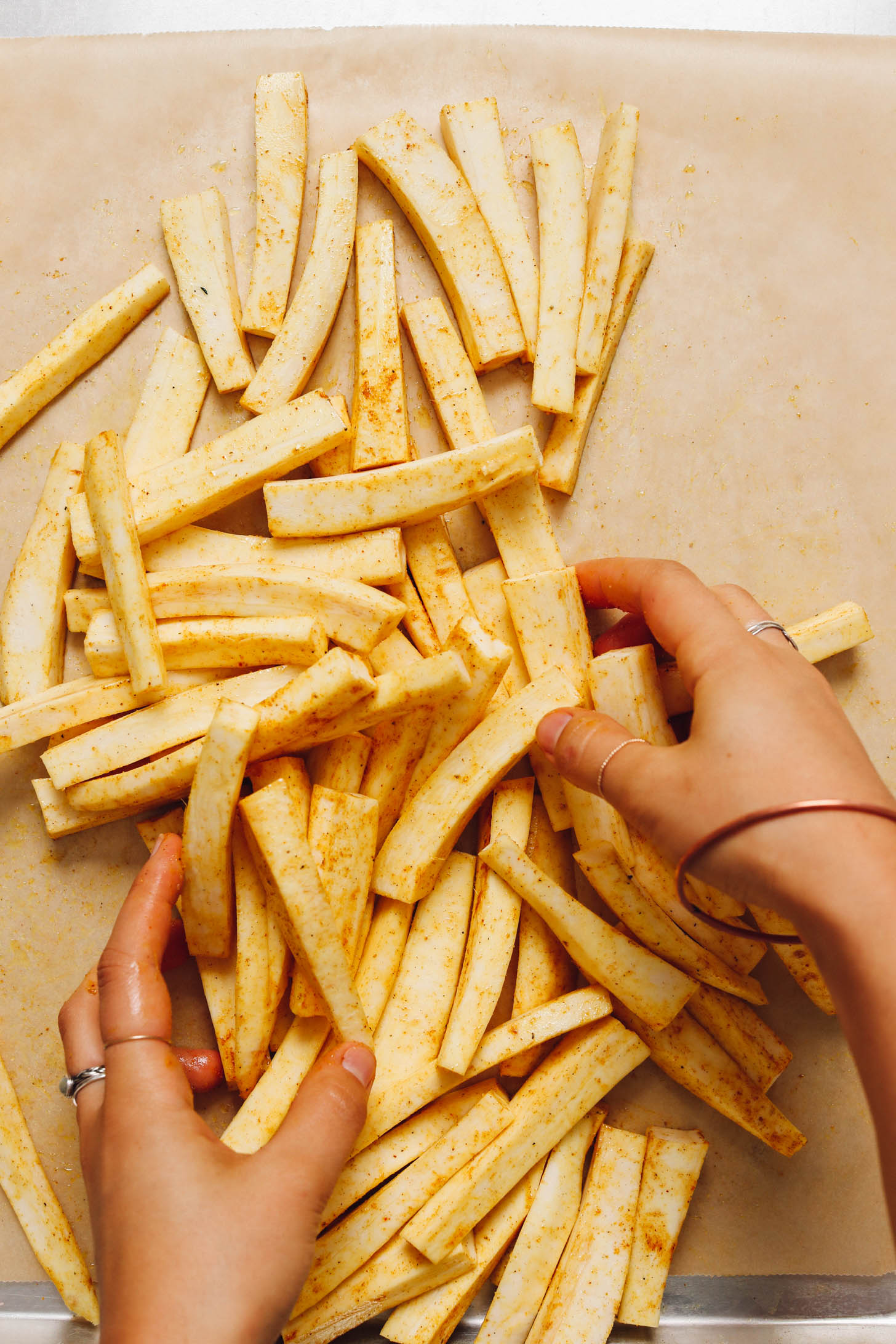 Tossing sliced parsnips in curry powder