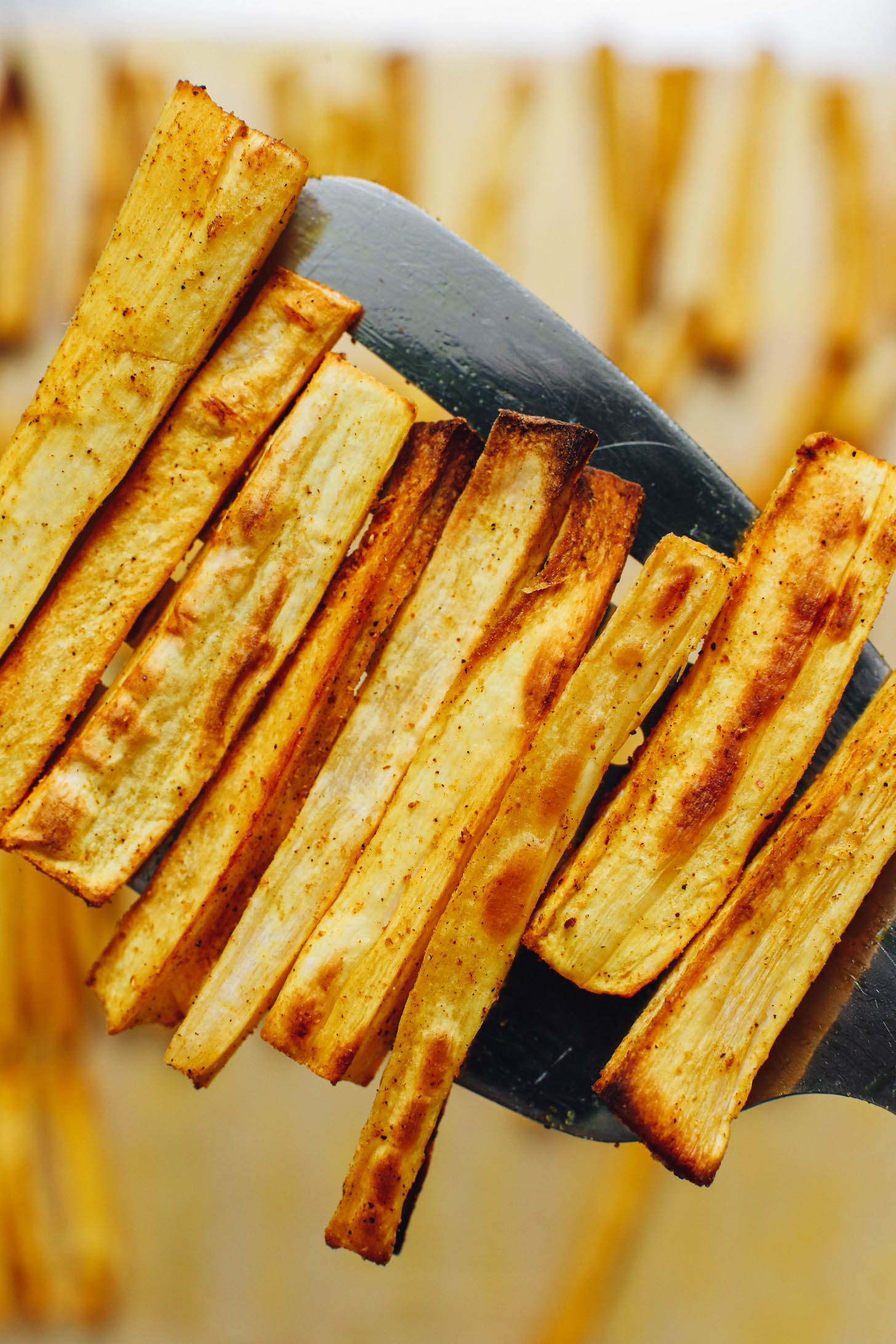 Holding up a spatula of perfectly roasted parsnip fries