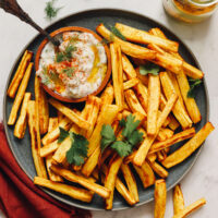 Baked parsnip fries on a plate with dairy-free yogurt sauce