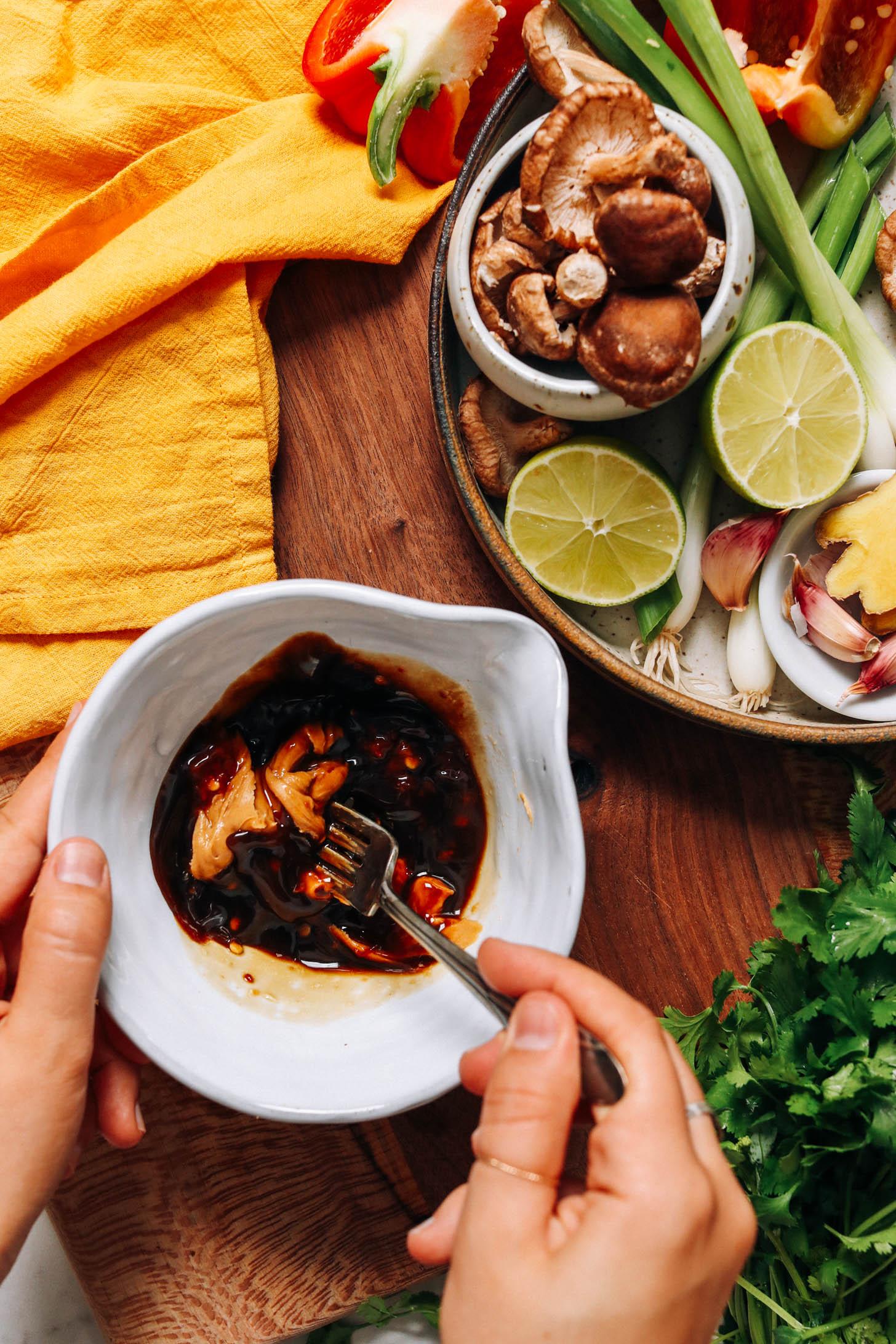 Bir kase fıstık ezmesi, hindistancevizi aminosu, akçaağaç şurubu, limon suyu ve acı sarımsak sosunu karıştırın
