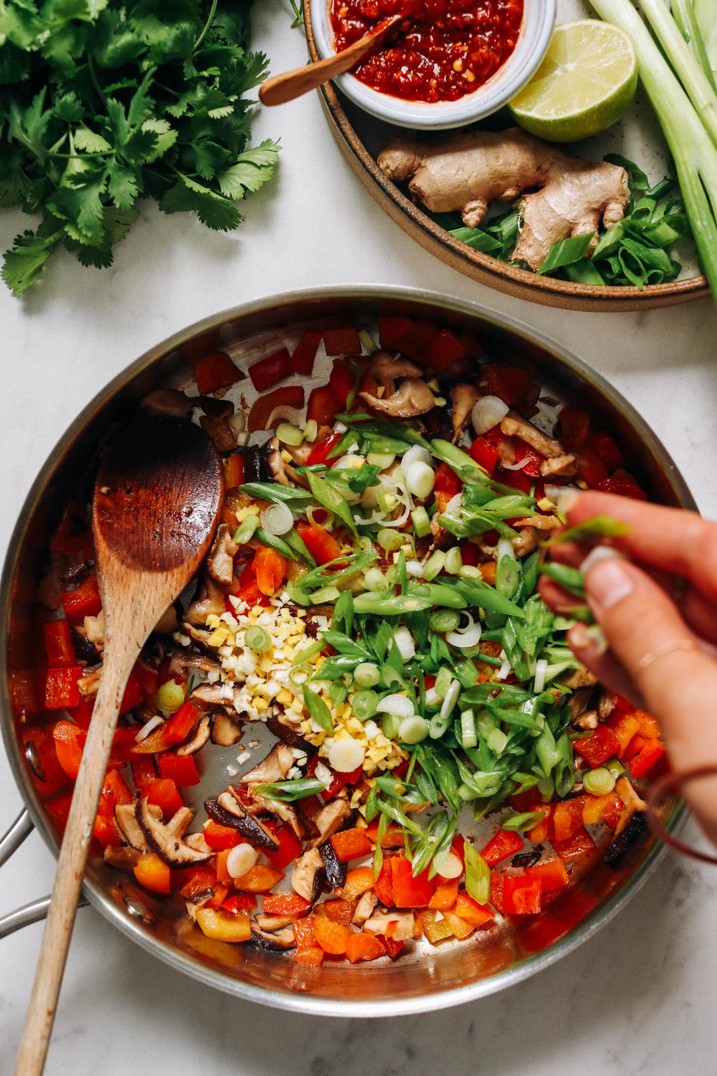 Sotelenmiş sebzelerden oluşan bir tavaya dilimlenmiş yeşil soğan ekleme