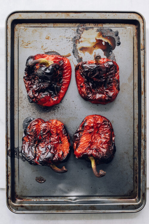 Baking sheet with four roasted red peppers