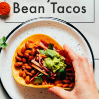 Plate and hand holding a vegan and gluten-free smoky bbq bean taco with guacamole on top