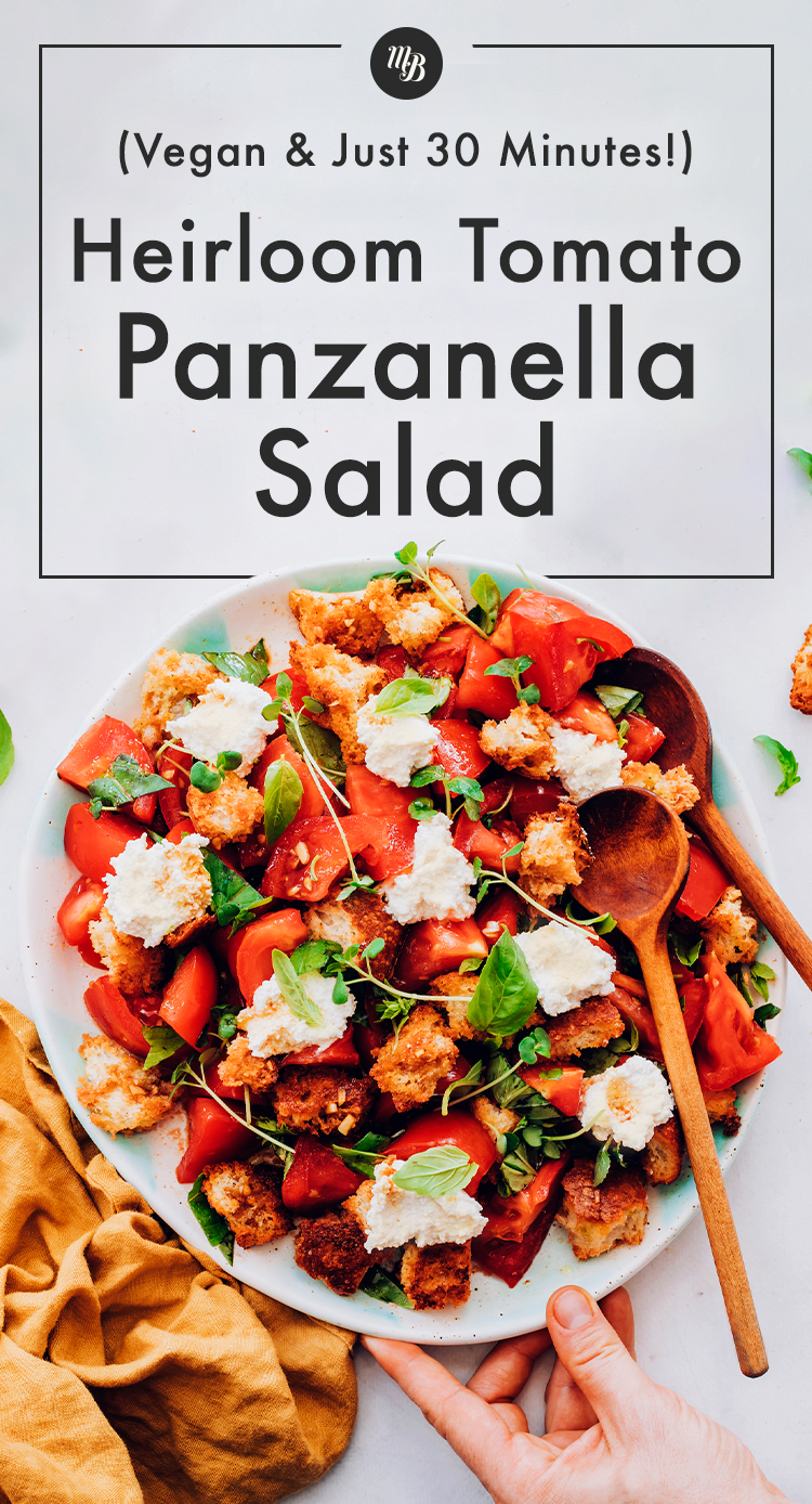 Bowl of vegan heirloom tomato panzanella salad with salad tongs in it