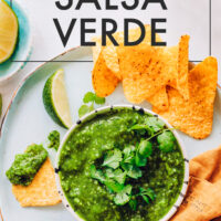 Bowl of roasted salsa verde on a platter with tortilla chips and lime wedges