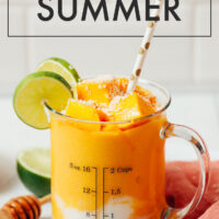 Glass of vegan mango lassi with chopped mango, shredded coconut, and lime slices on top