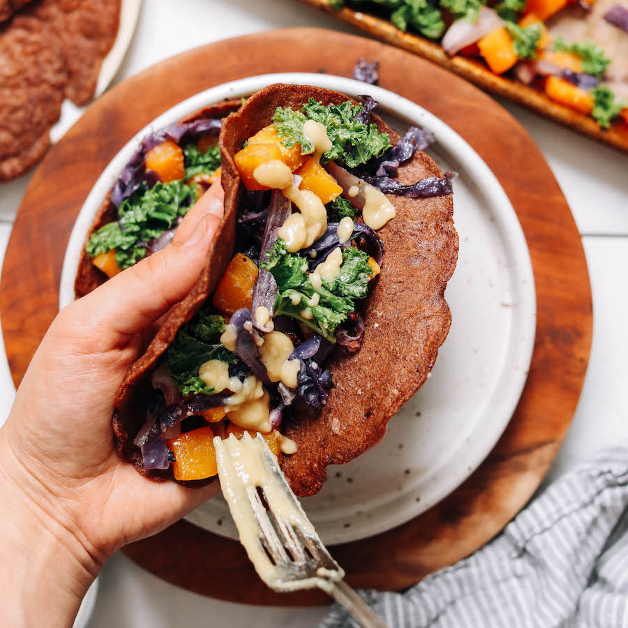 Adding miso sauce onto savory teff crepes with roasted vegetables