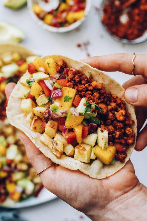 Holding a vegan chorizo breakfast taco
