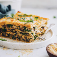Slice of butternut squash lasagna topped with vegan parmesan and fresh basil
