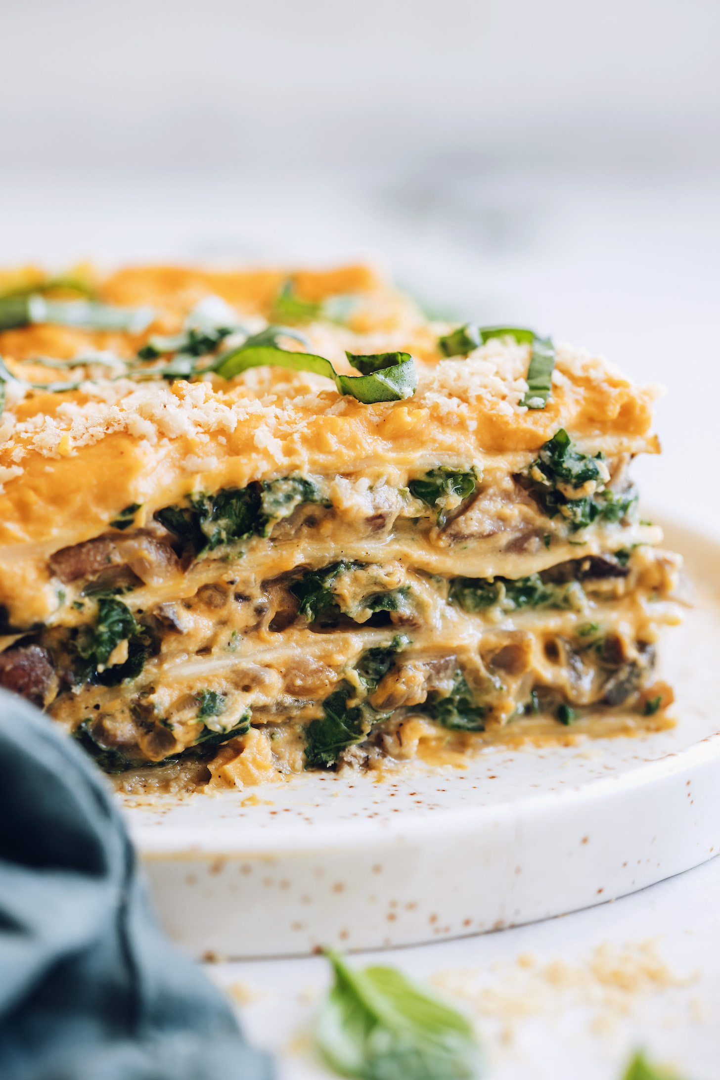 Close up shot of a slice of butternut squash lasagna topped with vegan parmesan and fresh basil