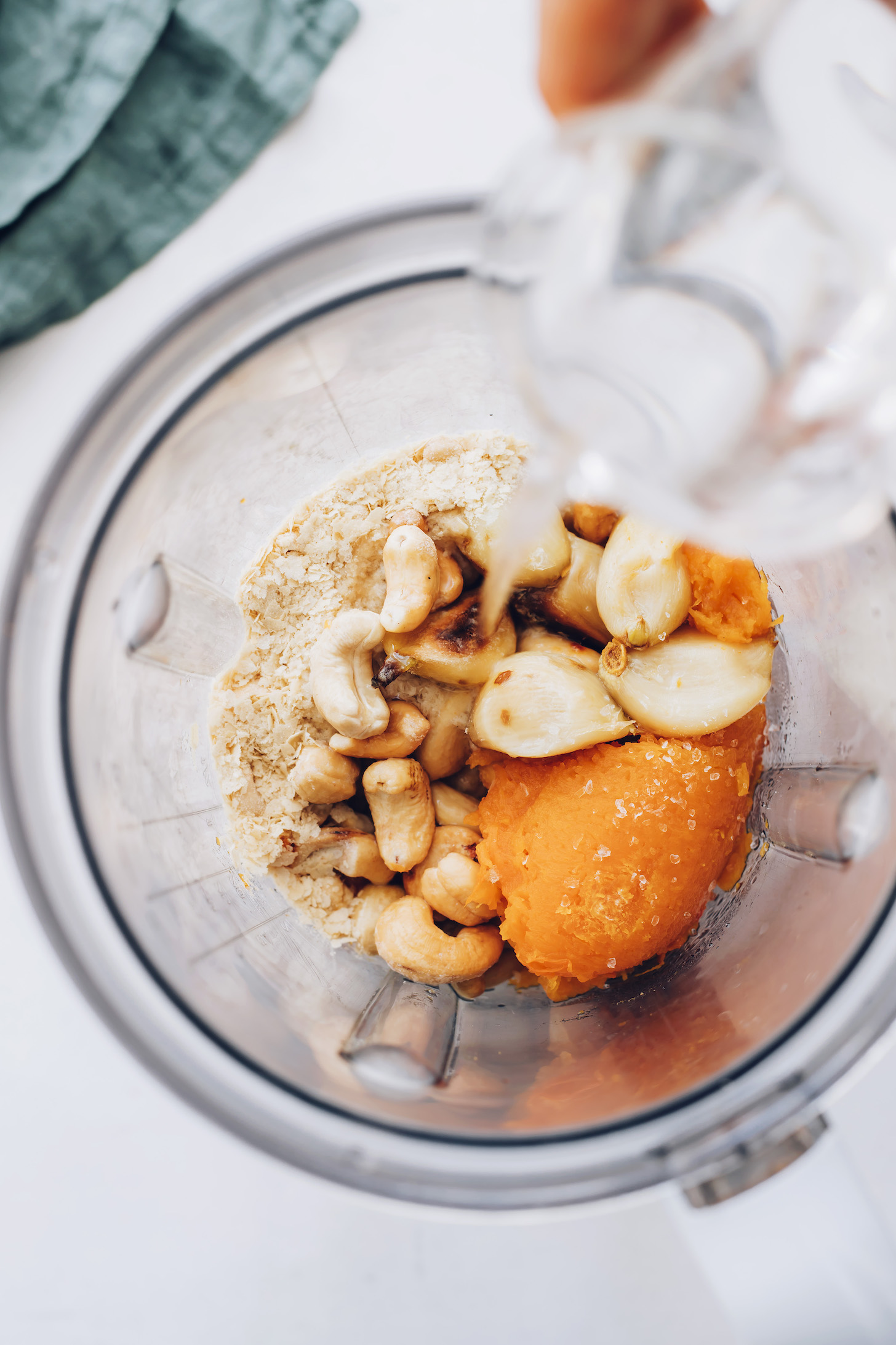 Pouring water into a blender with roasted squash, garlic, cashews, nutritional yeast, and salt