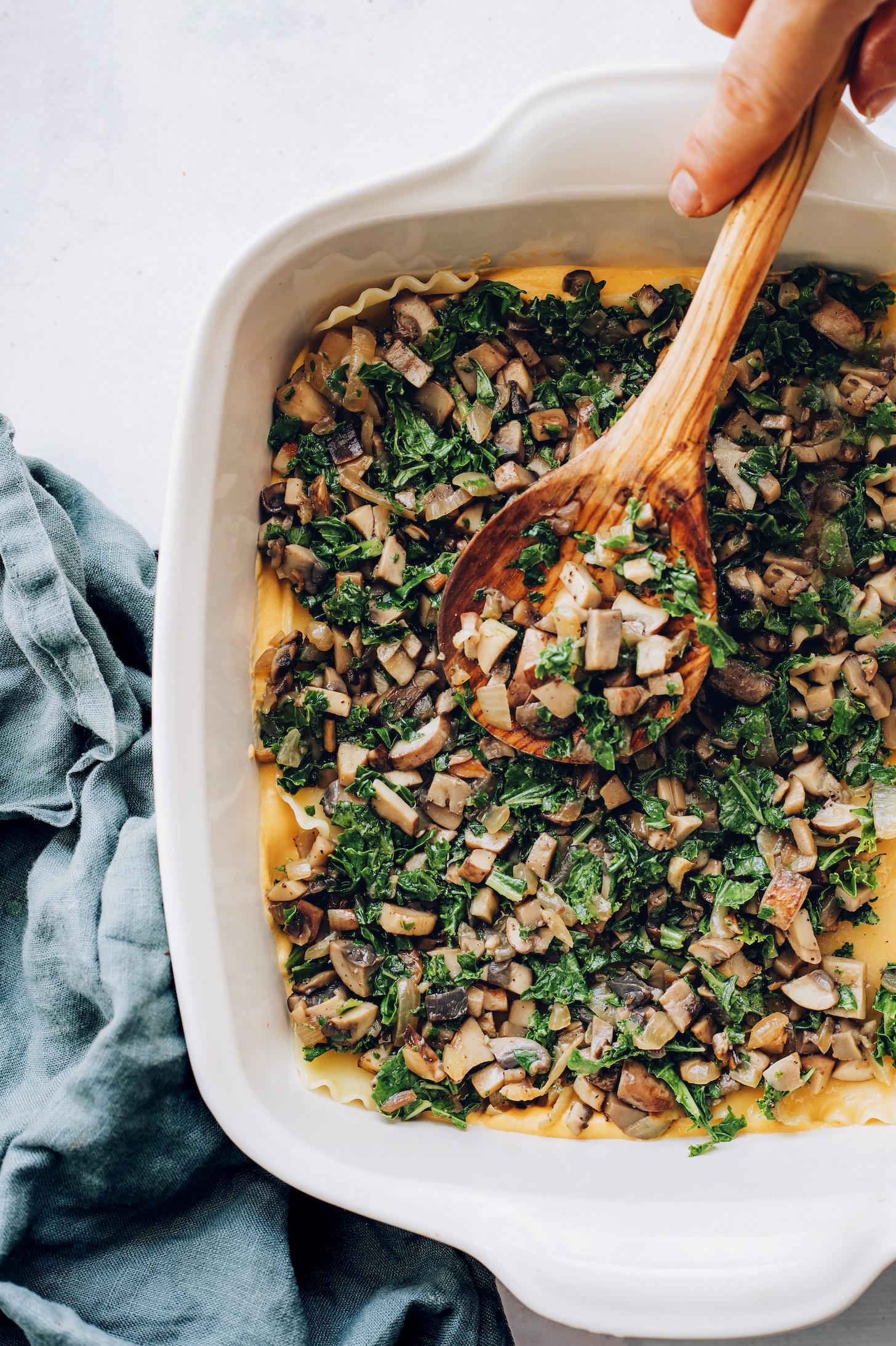 Layering mushroom kale filling over lasagna noodles