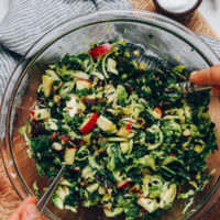 Tossing shaved brussel sprout salad with dressing