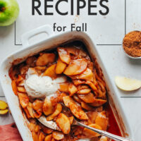 Dish of vegan cinnamon baked apples with vegan vanilla ice cream on top and a spoon in it