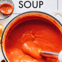Pot of vegan tomato soup being blended with an immersion blender
