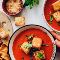 Bowl of vegan tomato soup with croutons and basil on top