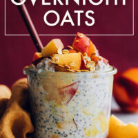 Jar of vegan and gluten-free peaches and cream overnight oats with fresh peaches on top and a spoon in it