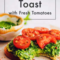 Slice of vegan pesto avocado toast with fresh tomatoes and a bowl of vegan pesto behind