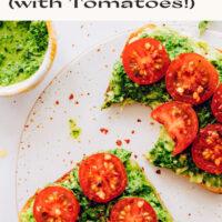 Slices of vegan pesto avocado toast with fresh tomatoes and a bowl of vegan pesto on the side