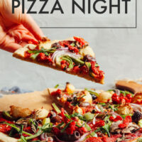 Hand picking up a piece of vegan and gluten-free cauliflower crust pizza