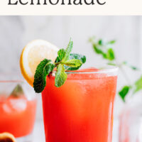 Glass of easy homemade strawberry lemonade with fresh lemon and mint on the side