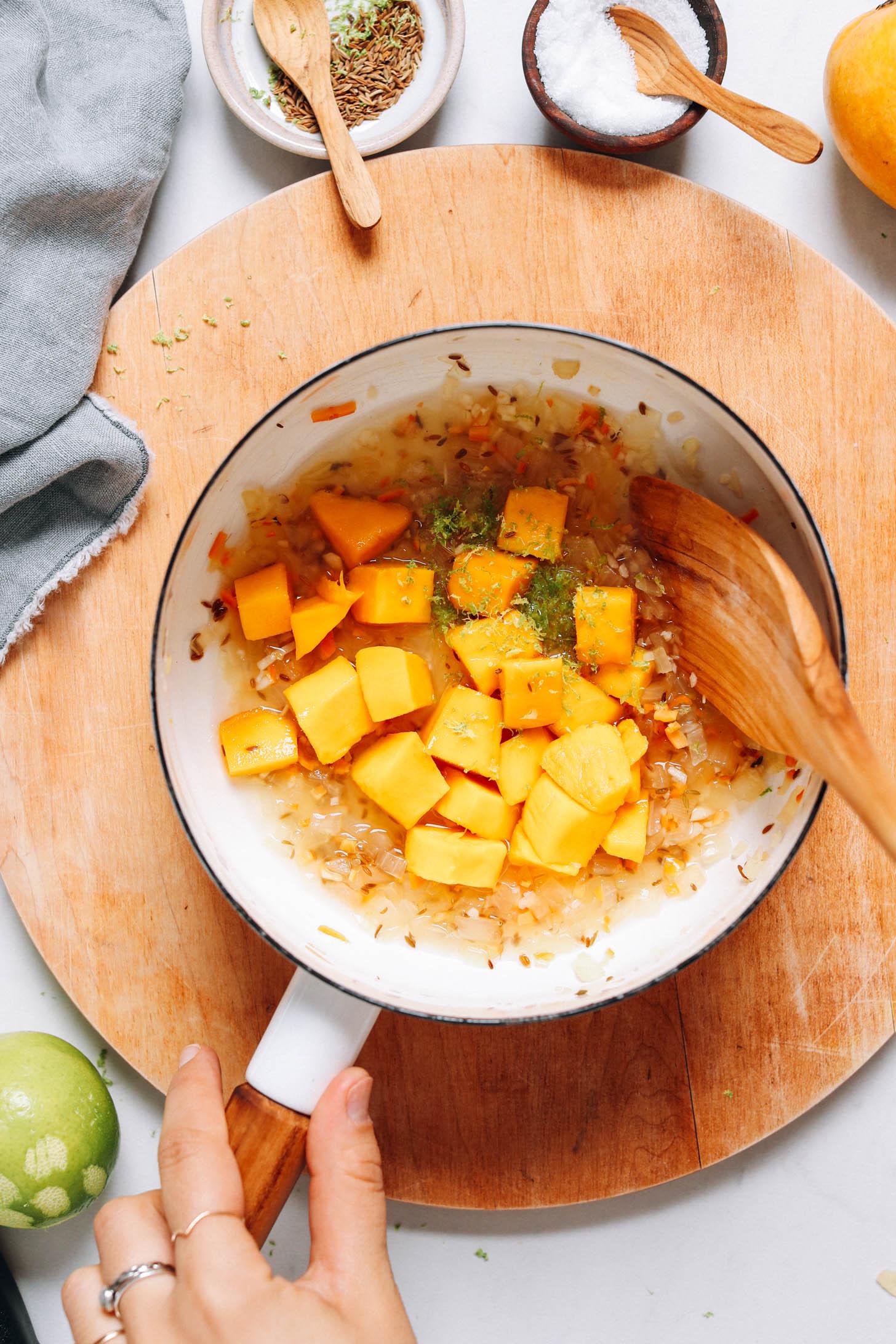 Saucepan of mango, sautéed onion, cumin seeds, lime zest, lime juice, water, and vinegar