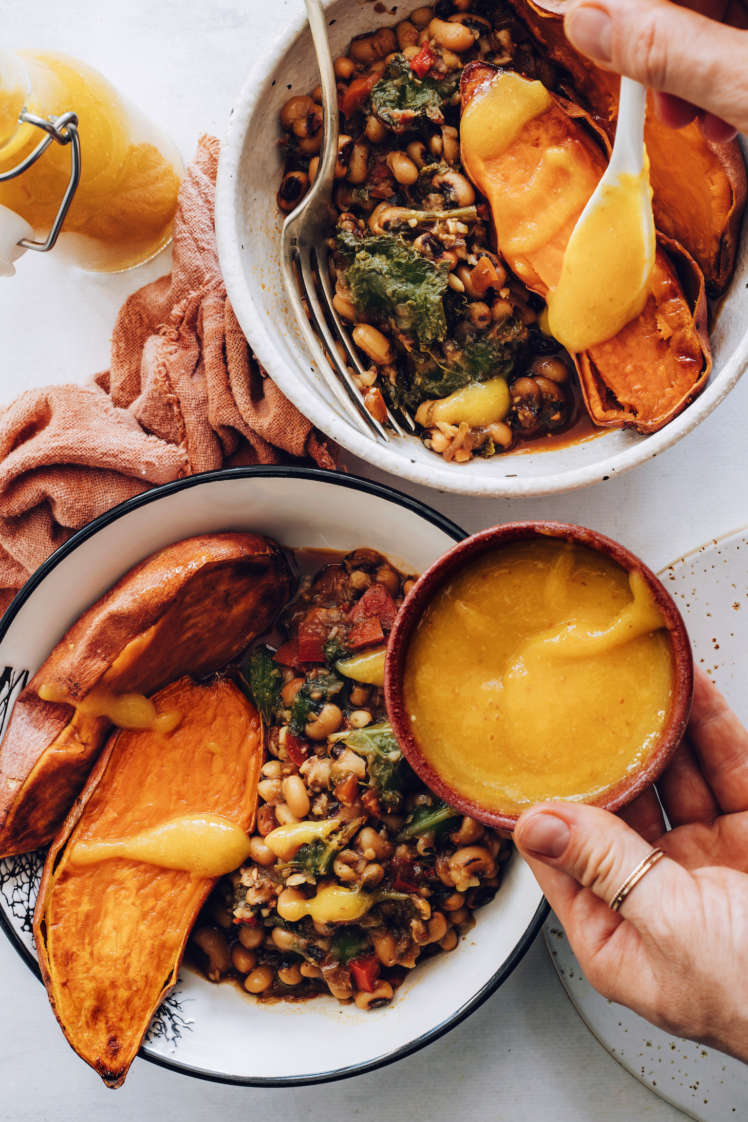 Adding hot sauce to sweet potato nourish bowls