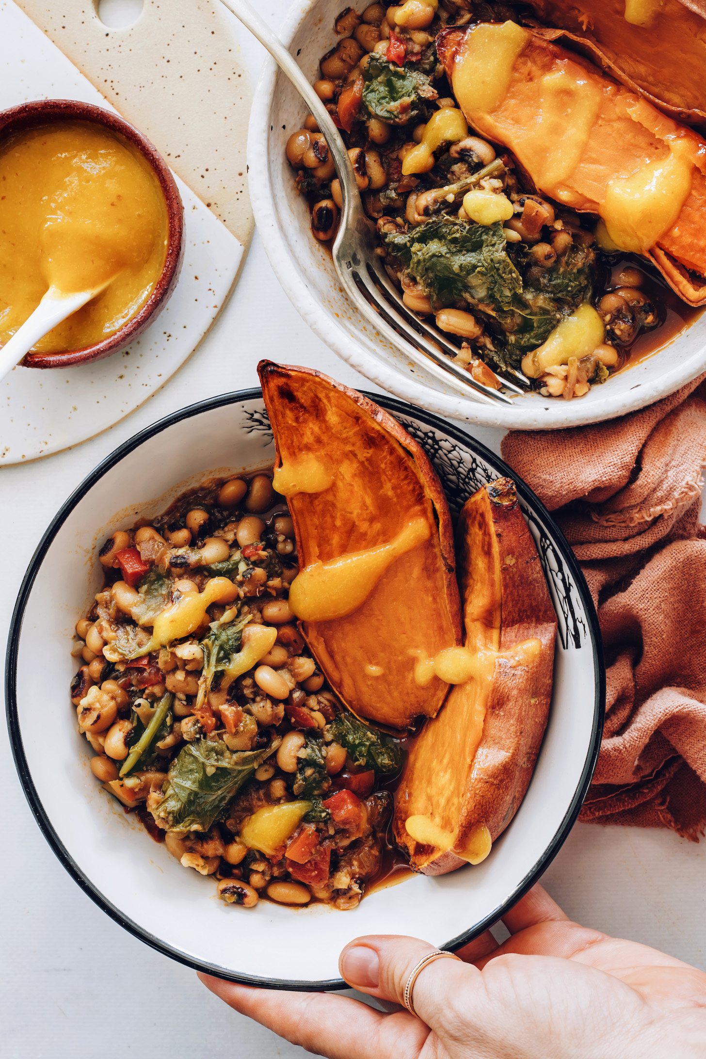 Holding a black eyed peas and greens nourish bowl with sweet potato and hot sauce