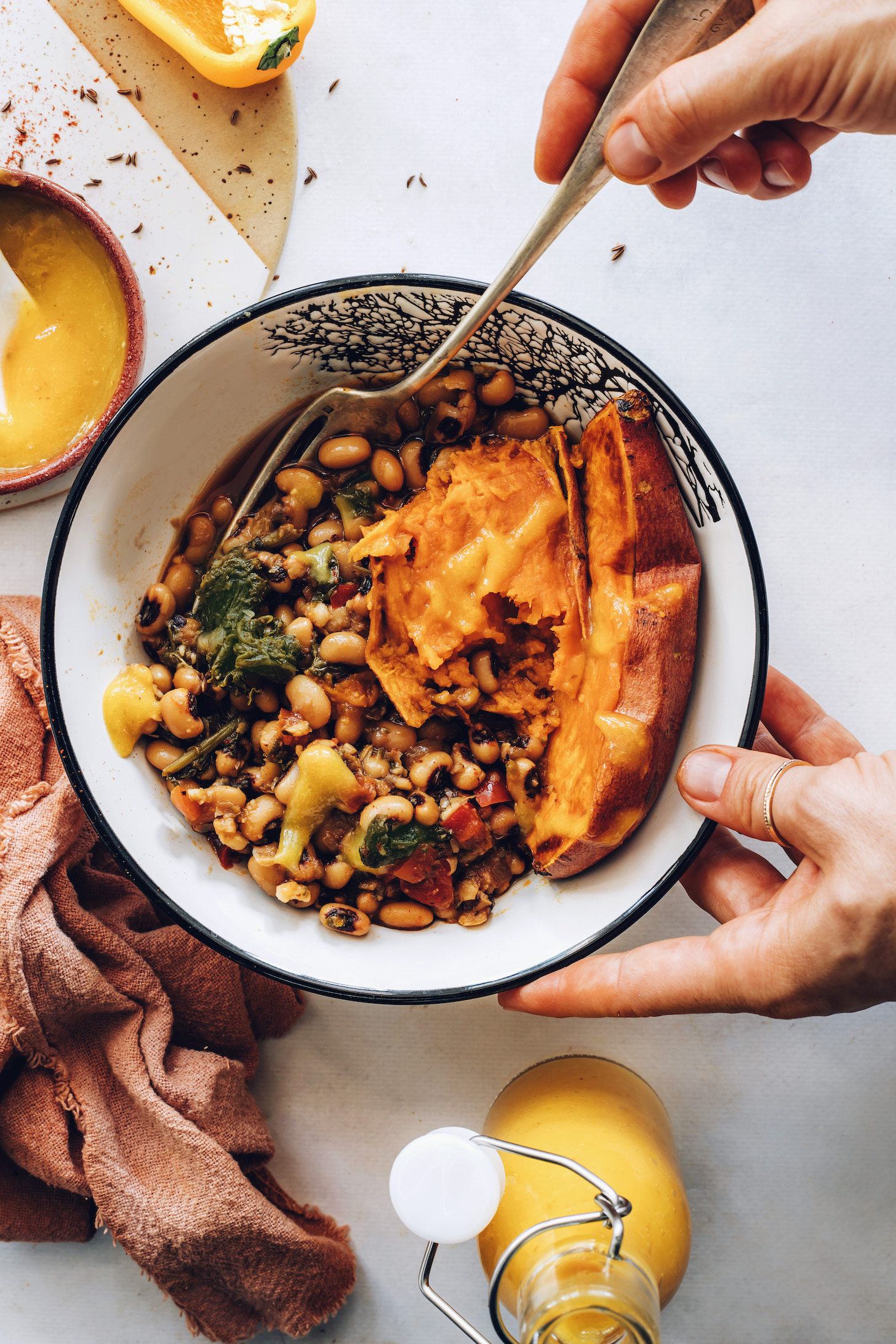 Holding a fork in a black eyed pea nourish bowl