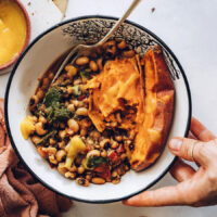Holding a nourish bowl topped with mango hot sauce