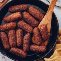 Cooking vegan chorizo sausage links in a skillet