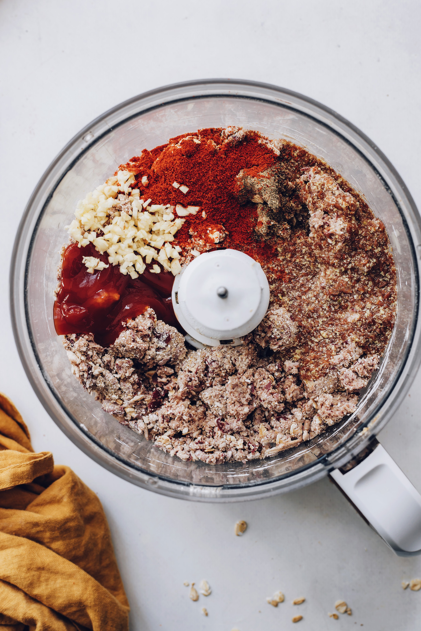 Ketchup, garlic, spices, and flax eggs in a bean, oat, and mushroom mixture