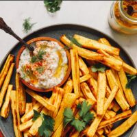 Plate of curry roasted parsnip fries with a dish of zesty dill yogurt sauce on the side