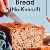 Knife slicing a loaf of vegan and gluten-free no-knead sandwich bread