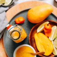 Jar of zesty mango habanero hot sauce with mango slices, lime wedges, and habanero peppers surrounding it