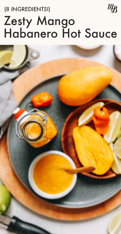 Etrafında mango dilimleri, limon dilimleri ve habanero biberleri olan lezzetli mango habanero acı sos kavanozu
