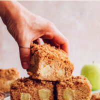 Hand holding a slice of vegan and gluten-free apple coffee cake