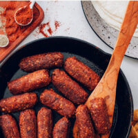 Cast iron skillet of vegan and gluten-free chorizo sausage links with a wooden spoon in it